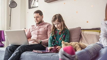 Father and daughter on sofa with laptop