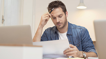 Man sitting at laptop and reading reports