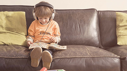 Young boy sitting on sofa with headphones on
