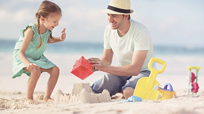Father and daughter building sand castles at the beach