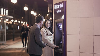 young couple smiling at a bank machine at night