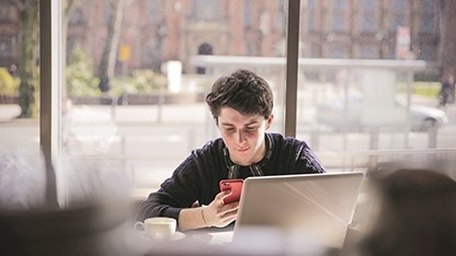 young guy in coffee shop with mobile